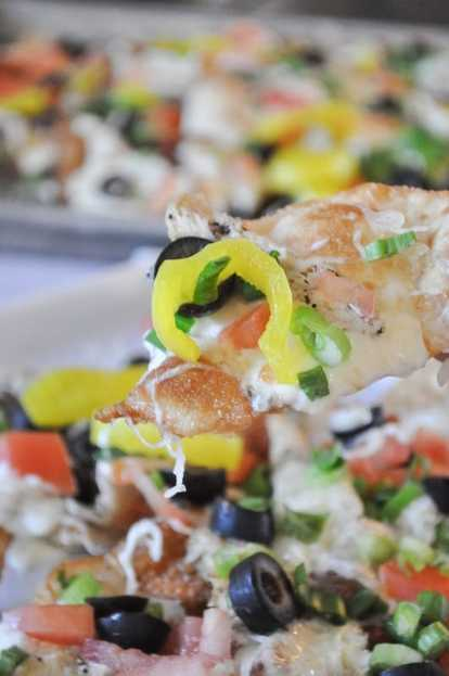 Crispy won ton wrappers topped with creamy alfredo sauce, chicken, cheese, banana peppers, tomatoes, green onions, and olives. These nachos are unforgettable.