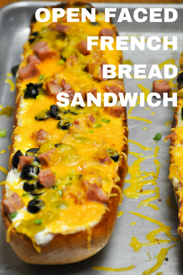Hot open faced french bread sandwich with green chiles, ham, olives, and cheddar cheese.