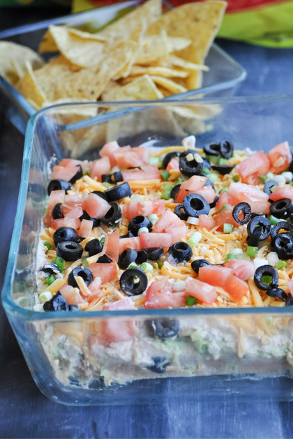 Refried beans, guacamole, sour cream/taco mix layer, cheddar cheese, green onions, tomatoes, and olives. This dip is unforgettable!