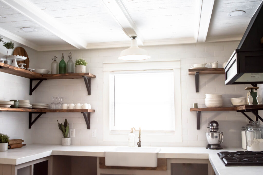 Kitchen with white backsplash and wood open shelving.