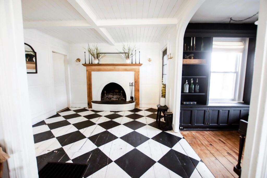 Painted Checkboard Floor on hardwood flooring. Easy flooring udpate. Budget flooring update. Old farmhouse floors. Harlequin flooring. Harlequin floors. Black and white floors.